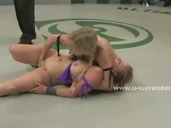 Two dominating lesbians kiss each other while sitting on a submissive lesbian face