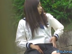 Kinky voyeur is watching while an Asian hot schoolgirl taking a piss in public and touching her self