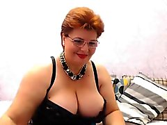 Buxom mature brunette in a green and black teddy shows off