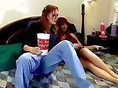 Hot lezzie bends her red-haired lesbian kitty friend down low and does her with a strap-on