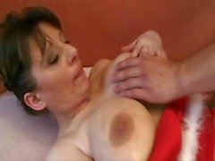 Brunette mom in a sexy Christmas nightie has big boobs ans a hairy pussy for fucking