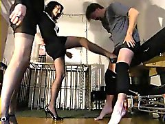 Two hotties are taking turns kicking his nuts and standing