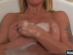 Tattooed angel relaxes in the bathtub