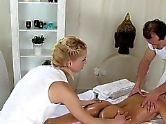 Two masseurs giving threesome massage