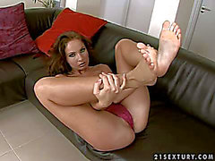 Slim brunette hair with lengthy legs plays with her feet