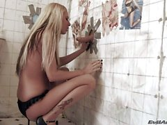 Big titted blonde Riley Evans gives head thru a glory hole