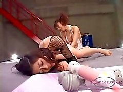 2 asian girls fighting stimulating and fucking each other with toys on the wrestling mat